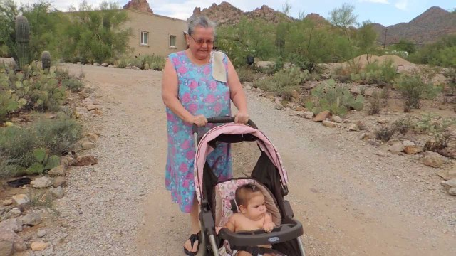 Cute chubby baby going for a walk with grandma in the desert